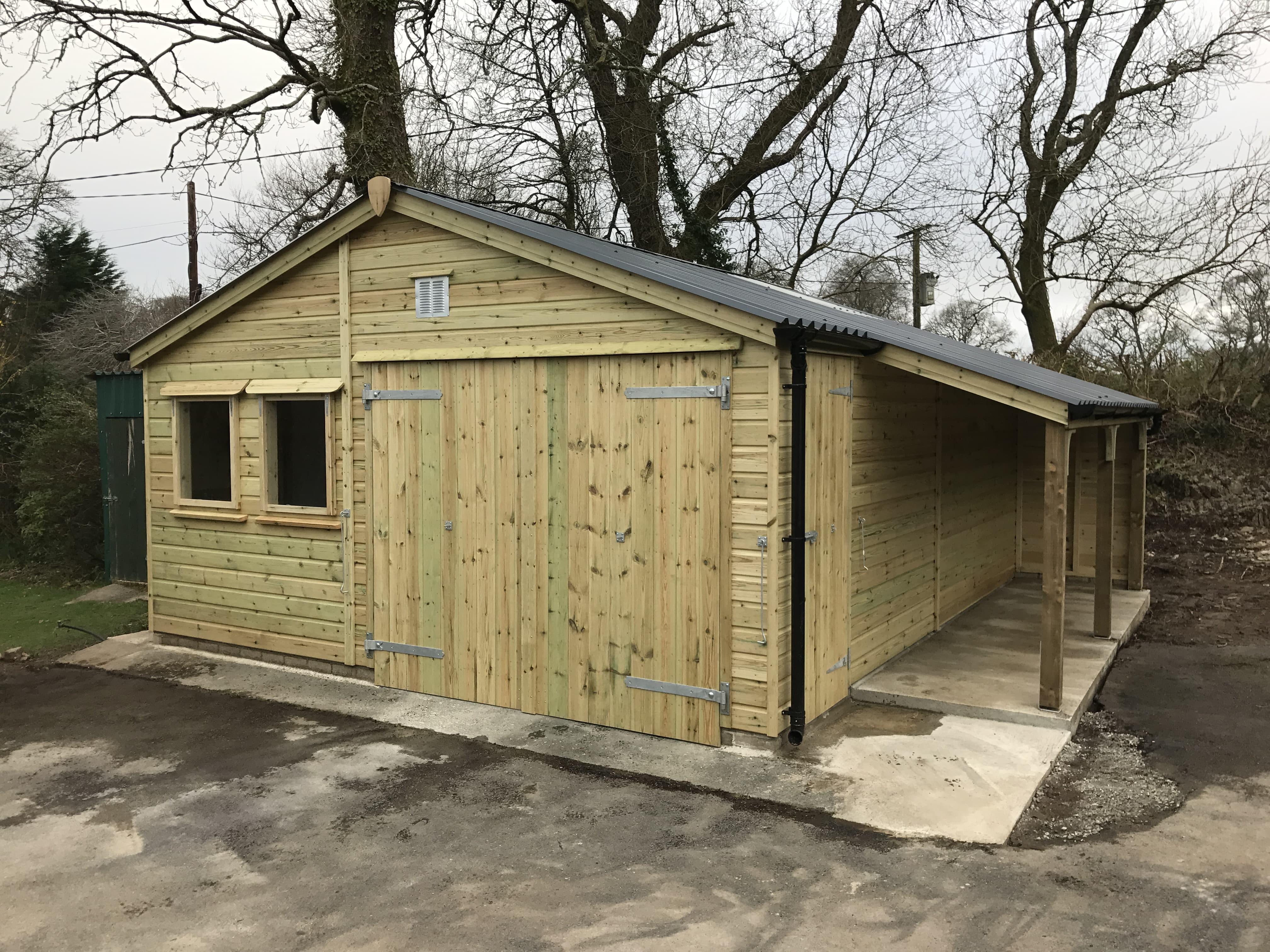 Wooden garage with lean to log storage