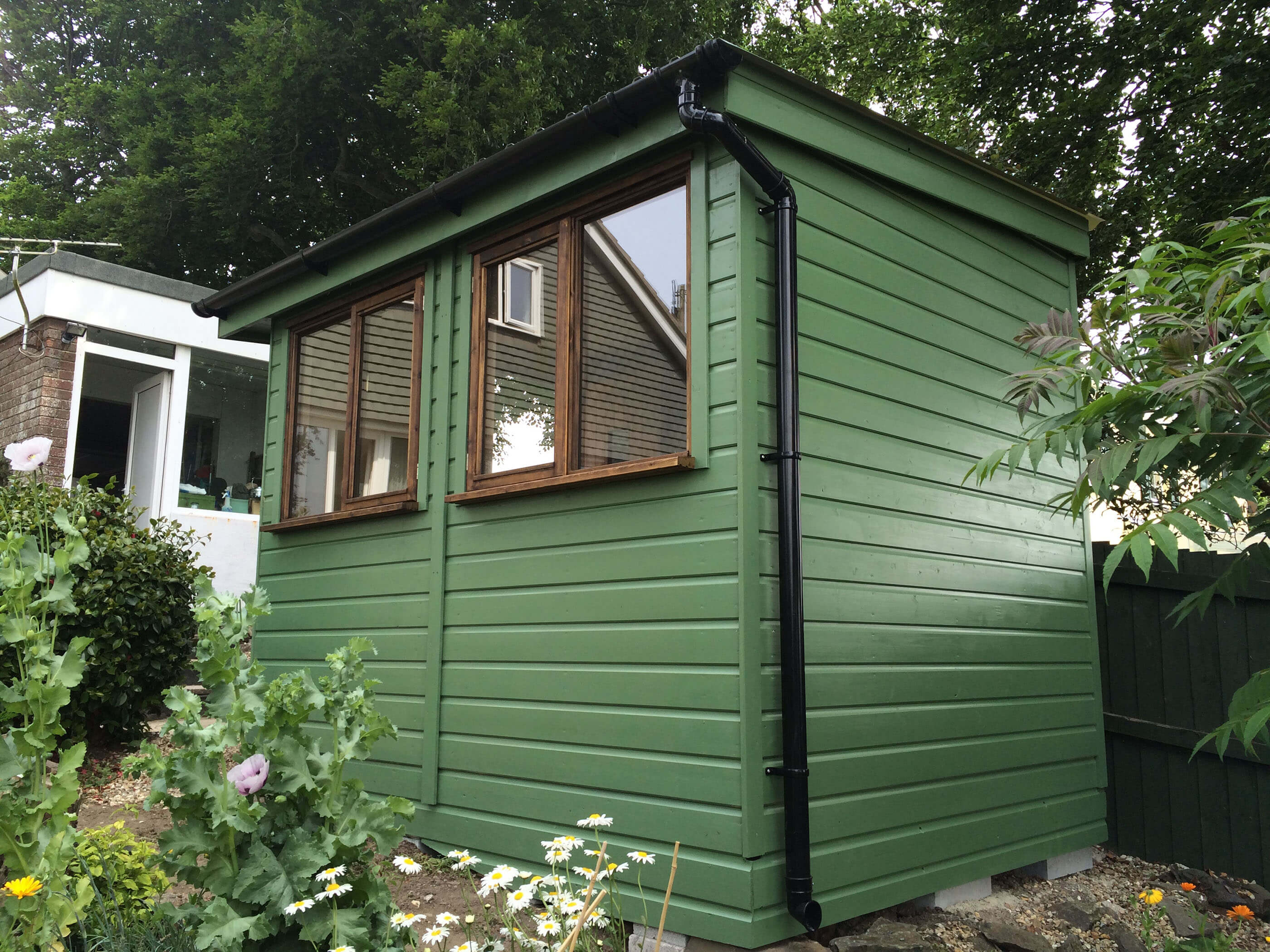 Small green garden office with pent roof