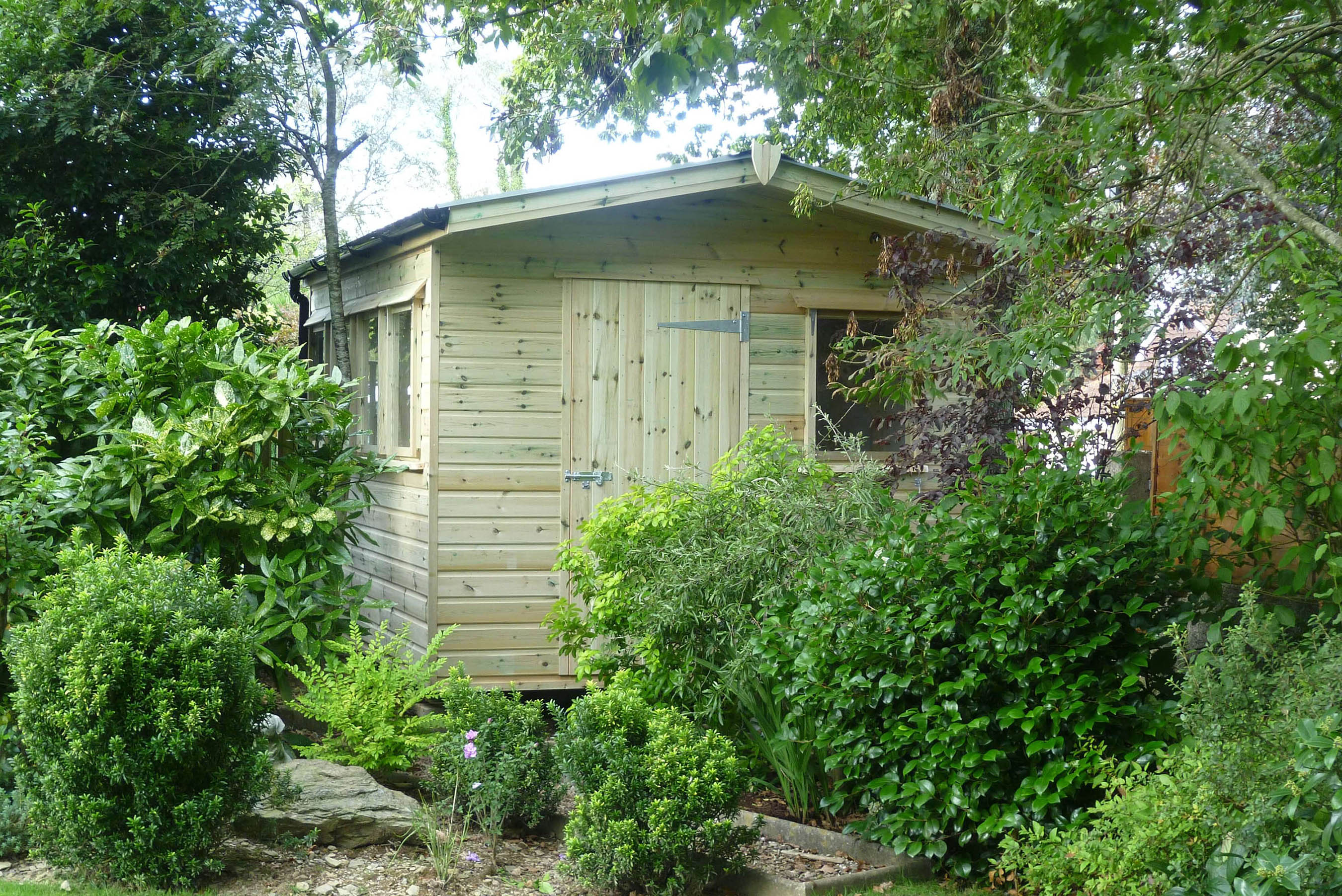 Garden shed with extended roof over entrance