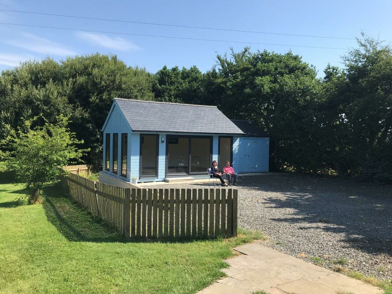 Painted timber garden studio with slate roof and full height windows